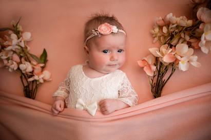 beautiful baby girl wearing a white lacy romper lying on a pink background surrounded by pink flowers for her studio baby photography session with starspeckled hearts photography in aldershot, hampshire