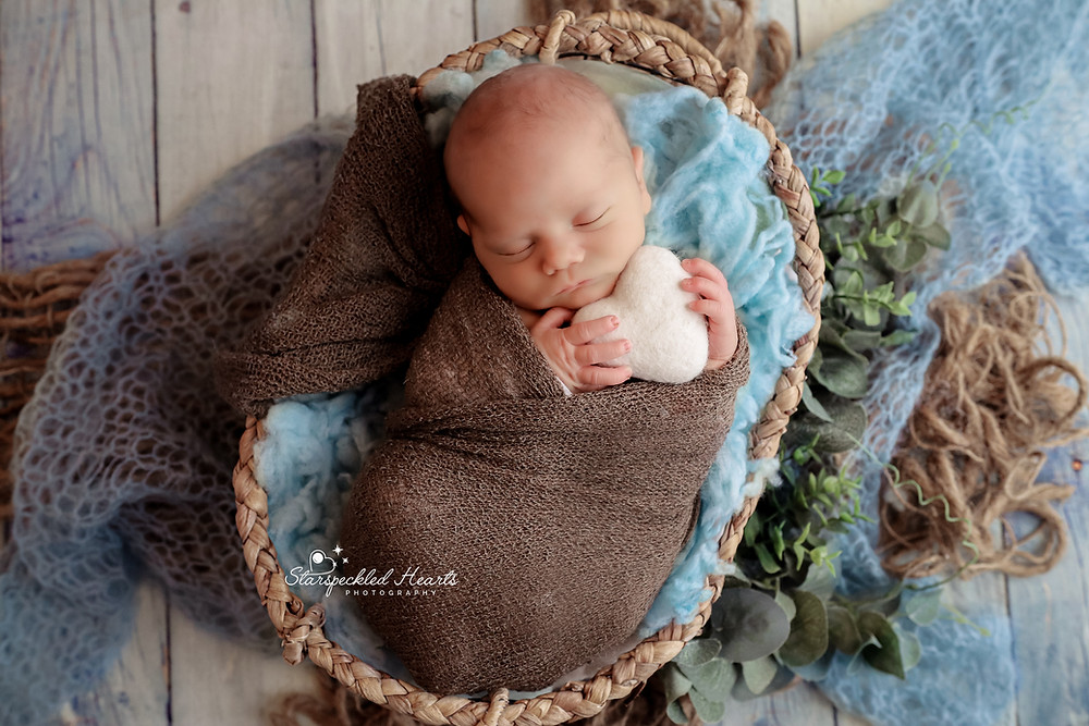 newborn wrapped in a brown swaddle holding a white felt heart, lying in a wicker basket filled with turquoise fluff for his newborn session with starspeckled hearts photography in reading