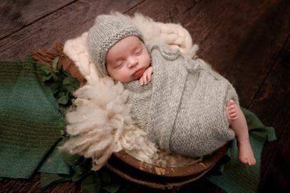 sleeping newborn baby boy wrapped in a grey knitted set