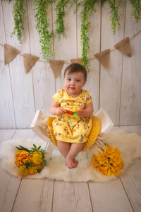 little girl wearing yellow easter themed dress holding felted carrot