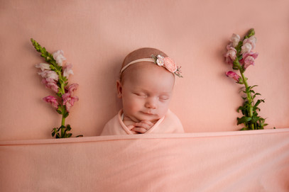 sleeping newborn girl wrapped in pink with flowers either side of her, tucked underneath a pink blanket with a little smile on