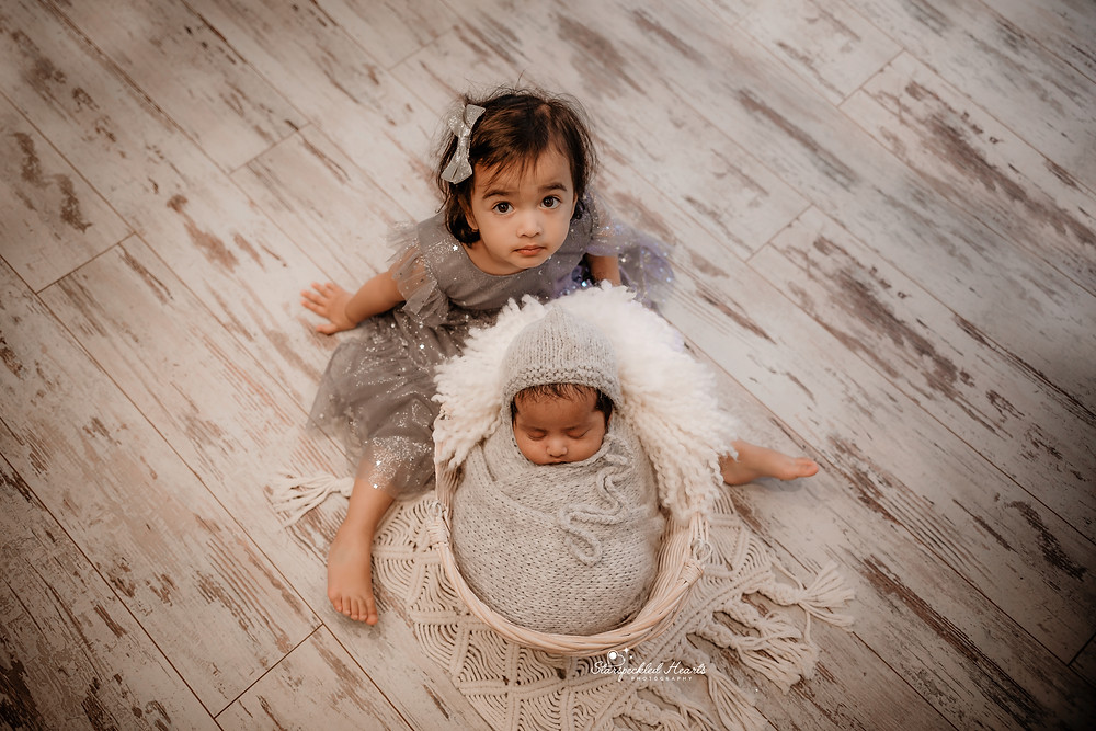 portrait of big sister and her newborn brother, the sister wearing a grey star print dress, sitting with her little brother in a basket in front of her