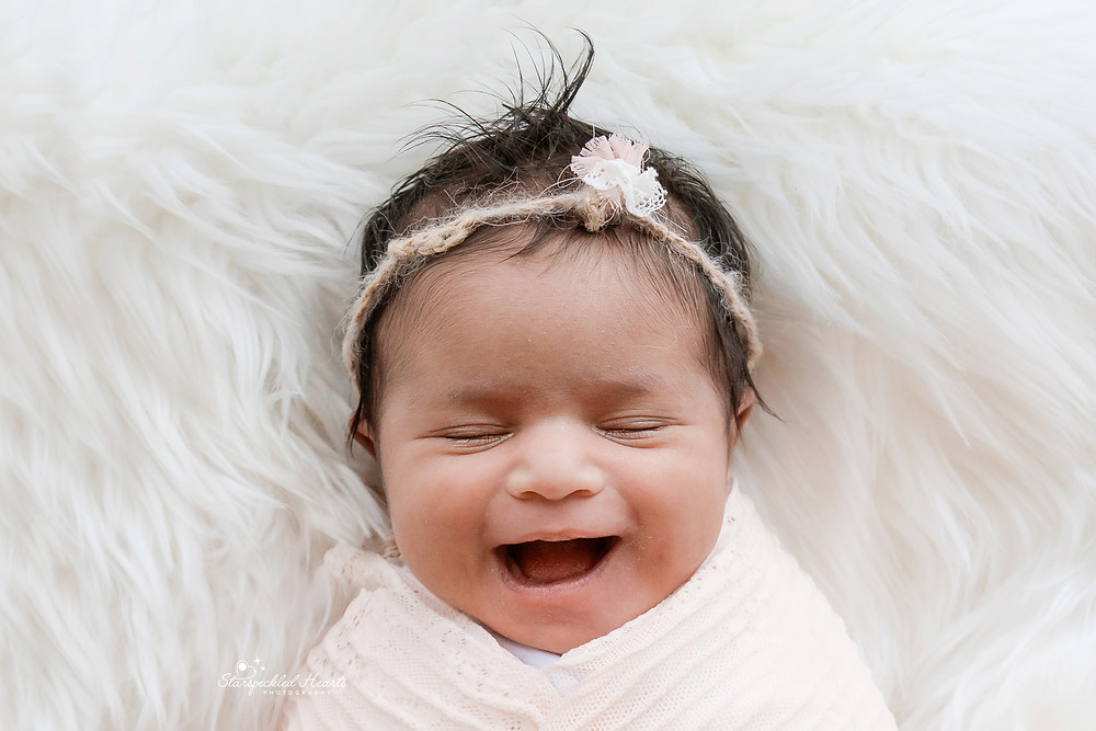 close up photo of newborn baby girl smiling at her newborn photography session in aldershot hampshire