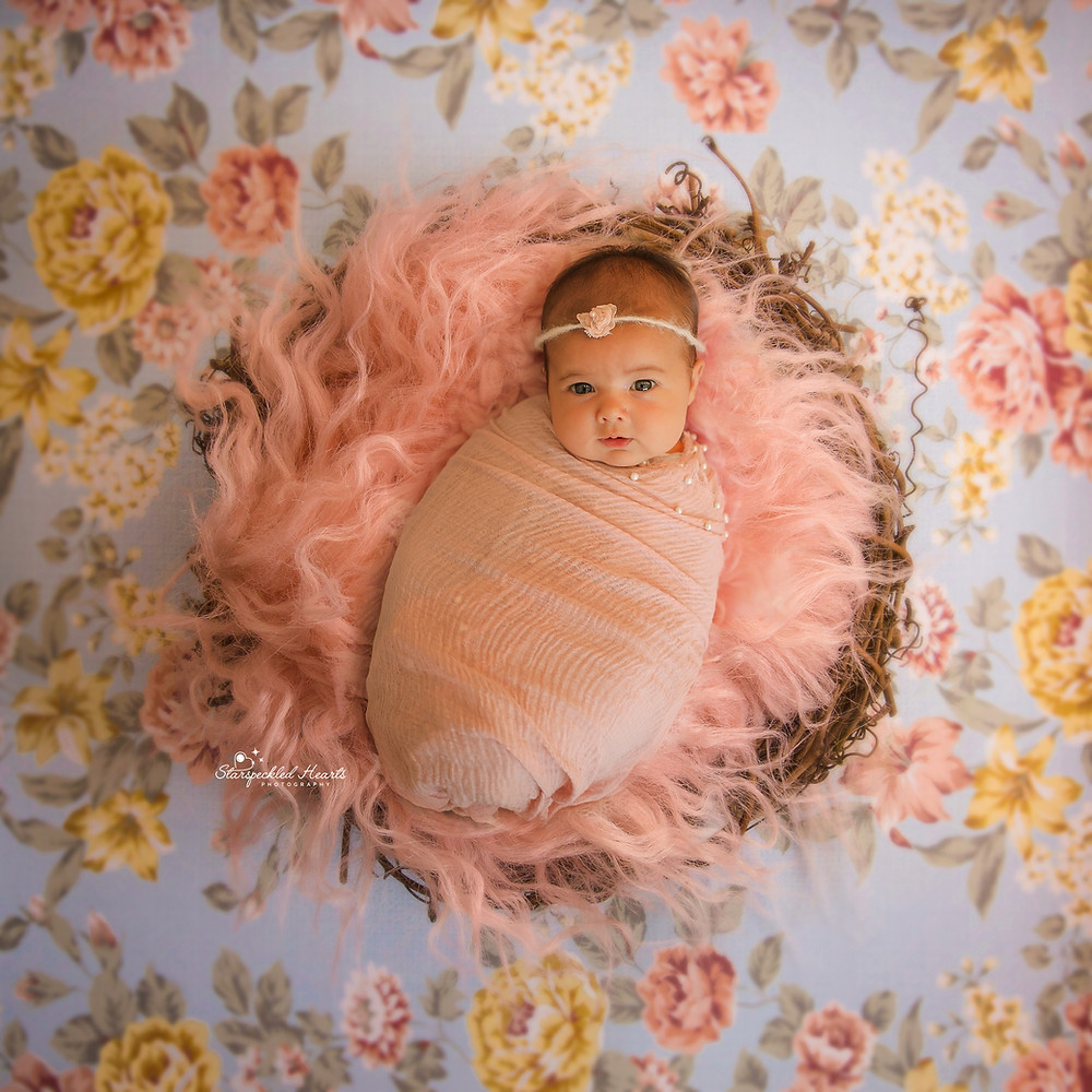 beautiful smiling baby girl wearing a pink pearl embellished wrap, laying in a wicker nest on a floral background