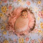 swaddled newborn baby lying in a basket on a floral backdrop