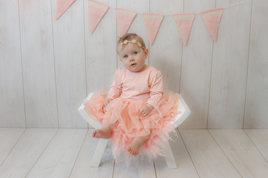cute baby girl wearing a pale pink tuille dress, sitting on a wooden curved stool in front of a white wooden wall with pale pink polka dotted bunting