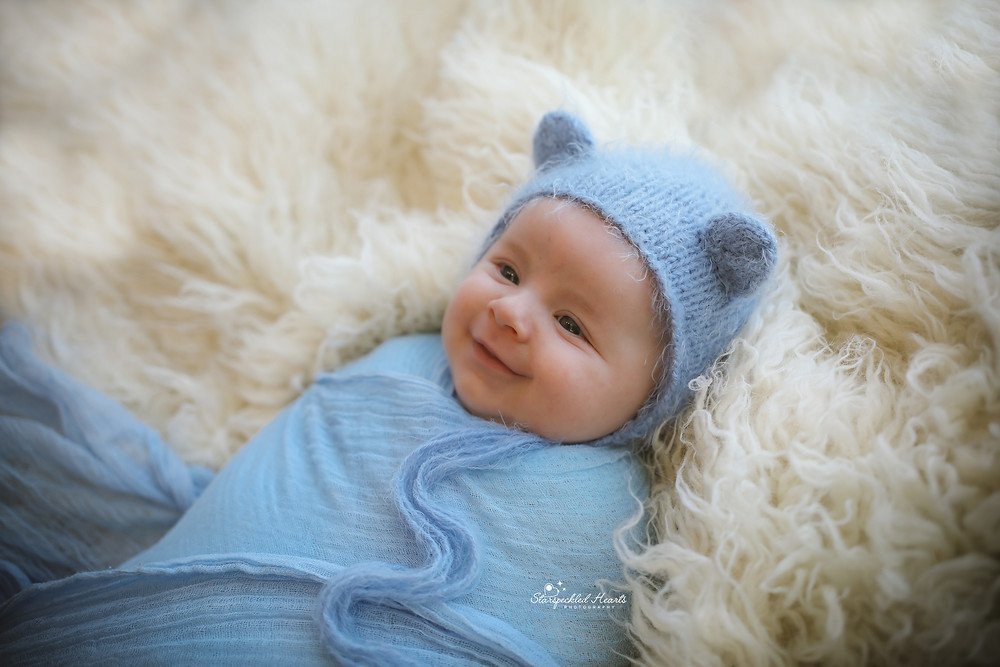 smiling baby boy wrapped in blue, wearing a matching blue bonnet with bear ears