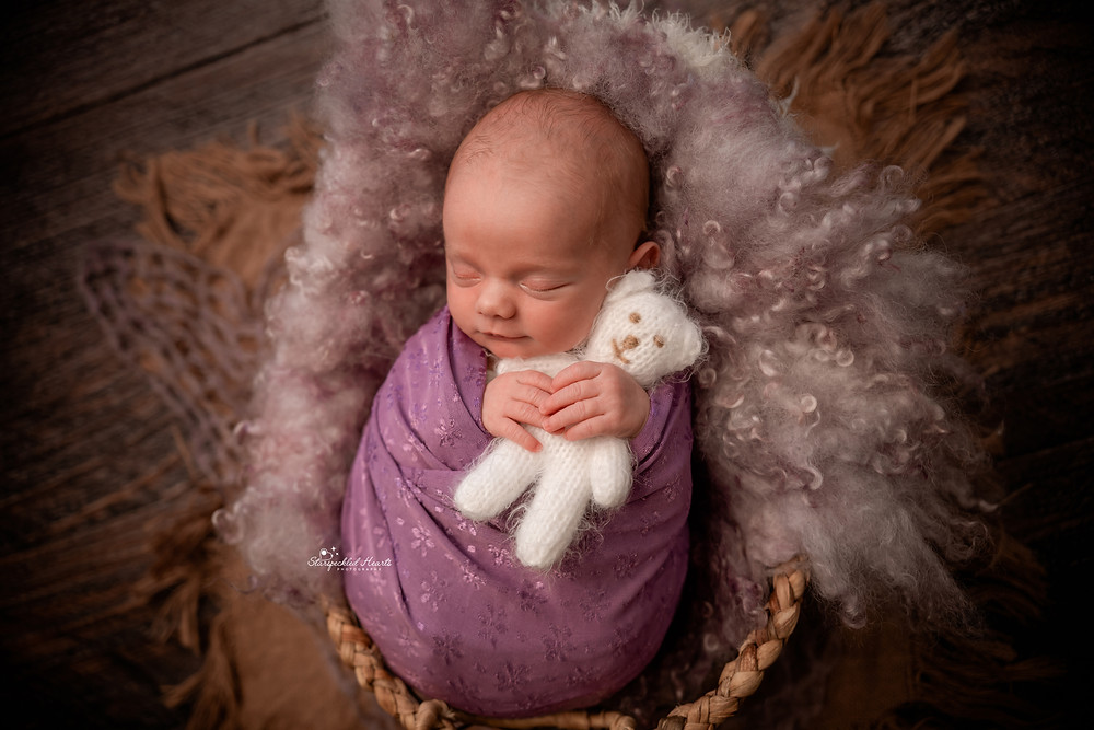 smiling baby girl wrapped in purple and cuddling a knitted white teddy for her newborn photography session in hampshire