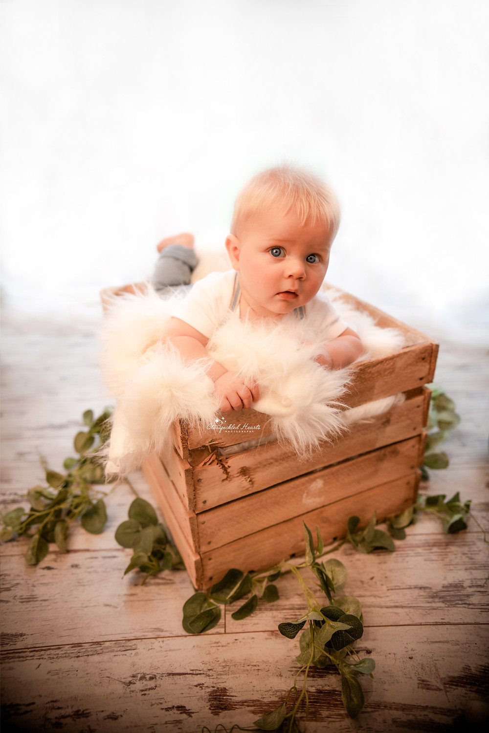 adorable baby boy lying in a crate surrounded by leaves