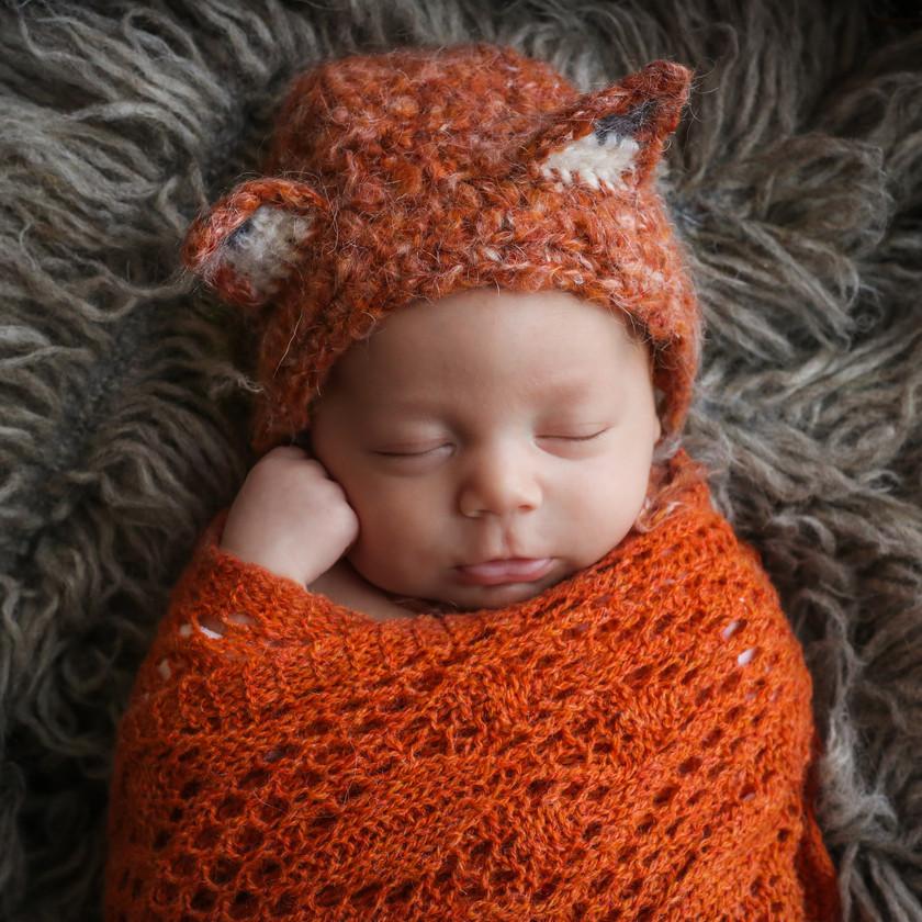 closeup of beautiful sleeping newborn wearing orange fox bonnet and wrap