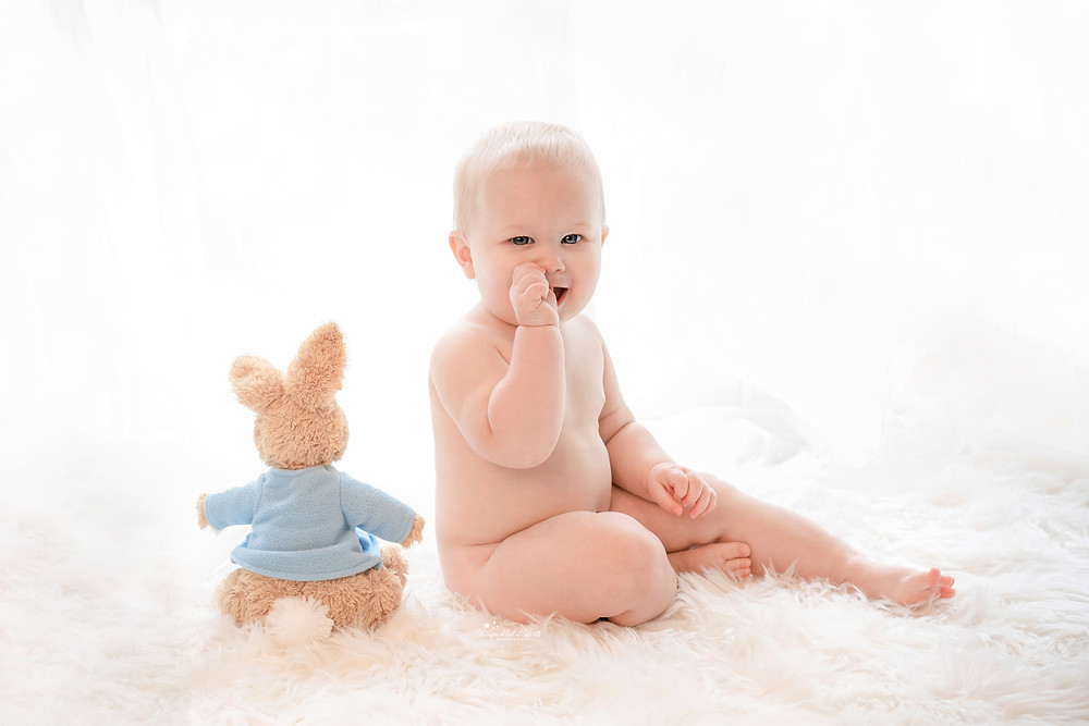 adorable blonde blue eyed baby boy sitting on a white fluffy rug with a peter rabbit teddy