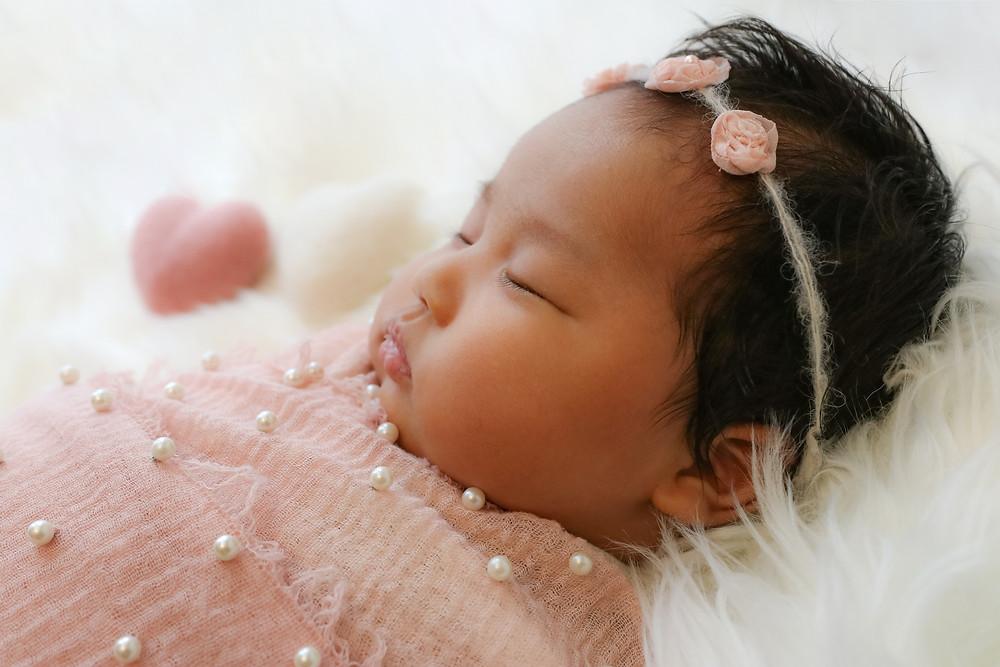 newborn girl in pink sleeping on white rug