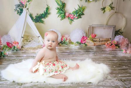 toddler girl sitting on white fur rug wearing floral skirt