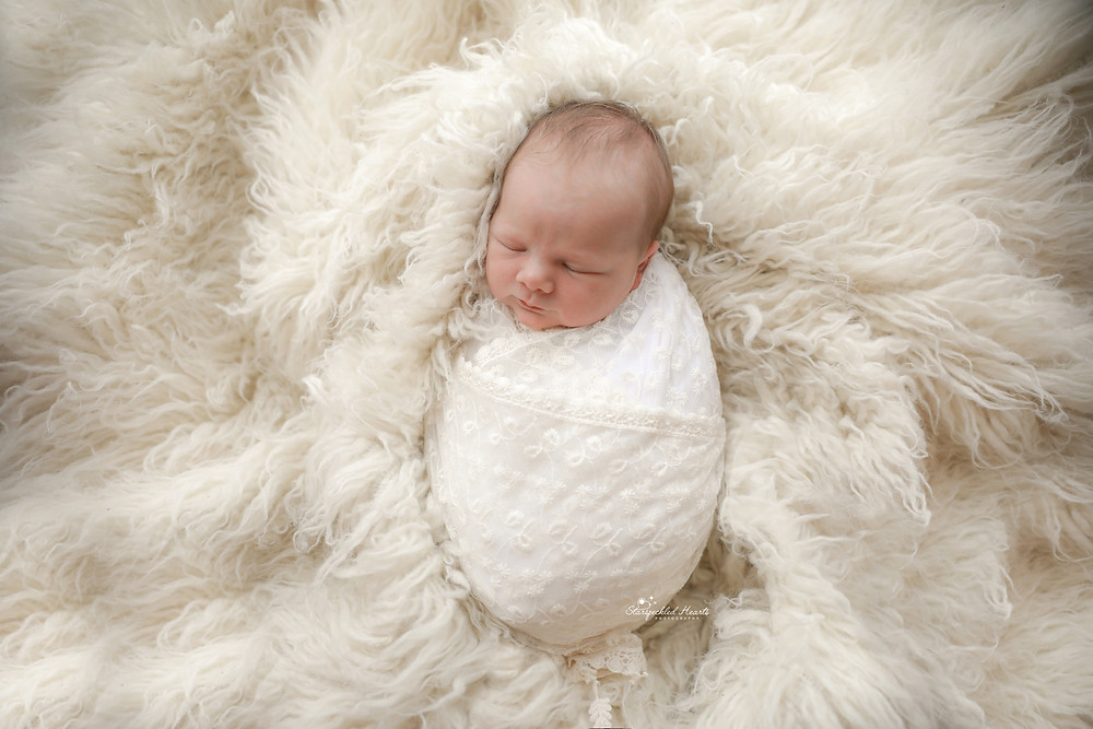 newborn baby wrapped in lace