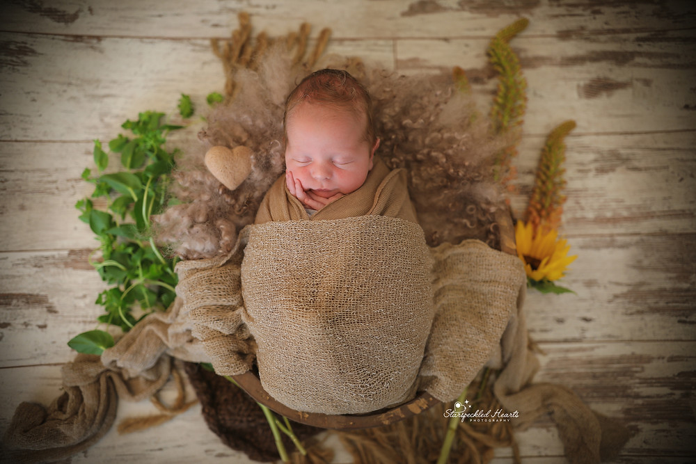 sleeping newborn wrapped in a brown swaddle, lying in a wooden bowl surrounded by greenery and flowers