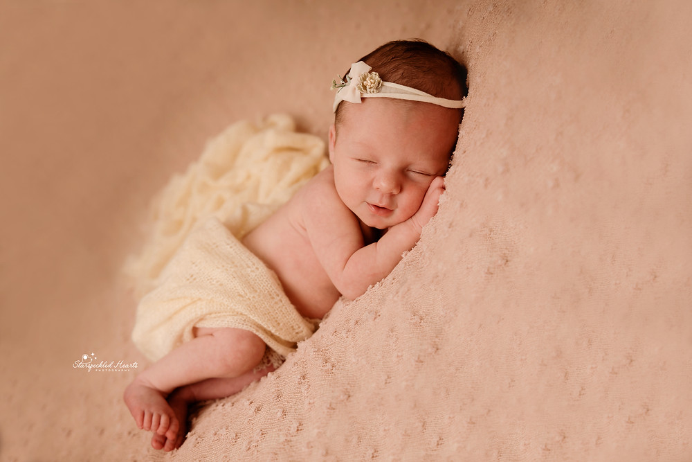 sleeping newborn girl lying on a pink textured blanket for her newborn photography session with starspeckled hearts photography in hampshire