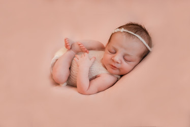 baby girl lying on her back on a pink backdrop