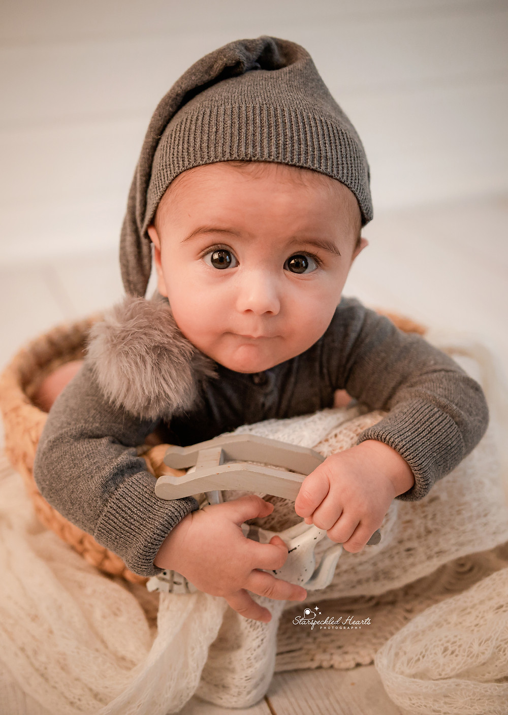 baby boy with big brown eyes wearing a grey ribbed romper suit with a matching sleepy cap for his baby photography session in Hampshire