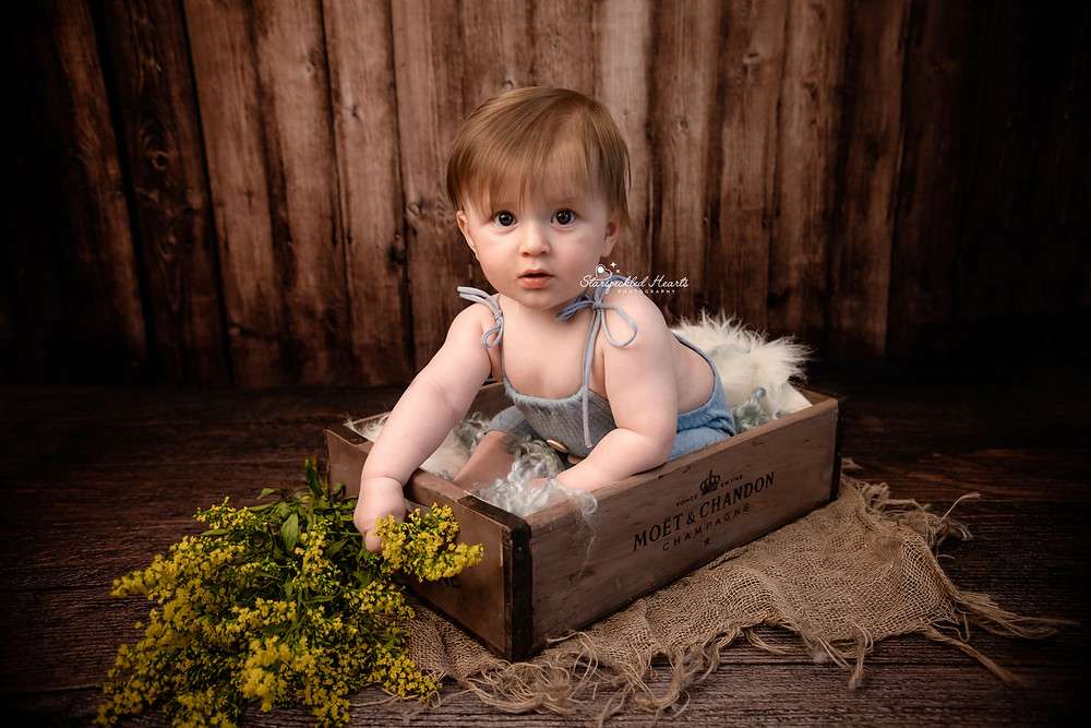 adorable baby boy sitting in a moet and chandon wine crate wearing a blue ribbed romper