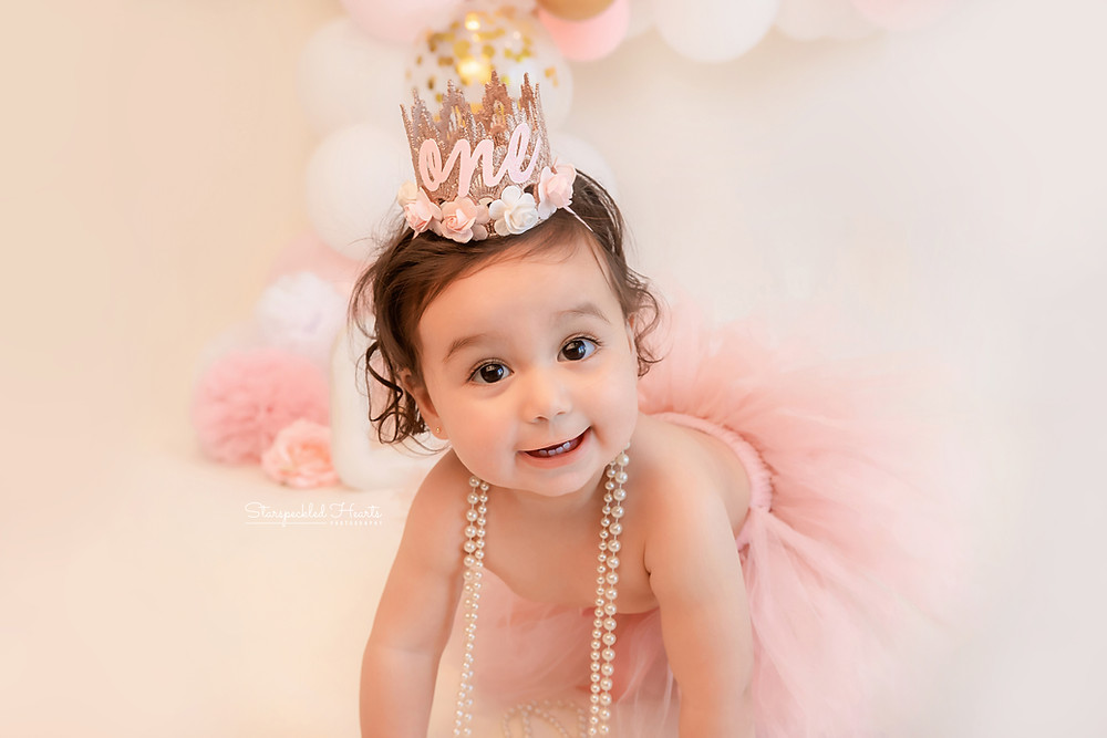 pink and gold themed 1st birthday cake smash session for adorable baby girl in aldershot, hampshire