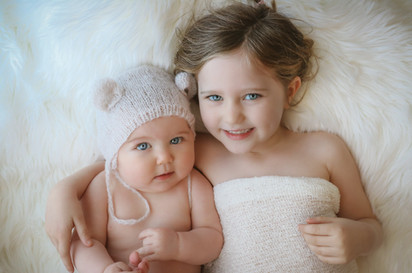 a smiling toddler girl and a baby boy with arms around eachother, laying down on a white rug