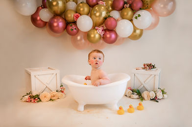 cute baby girl sitting in a clawfooted tub with a pink, gold and white balloon garland over her, surrounded by flowers