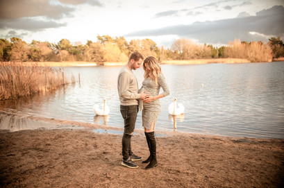a pregnant woman and her husband in an embrace, standing near a large lake with two swans in the background for their outdoor maternity session with starspeckled hearts photography in aldershot hampshire