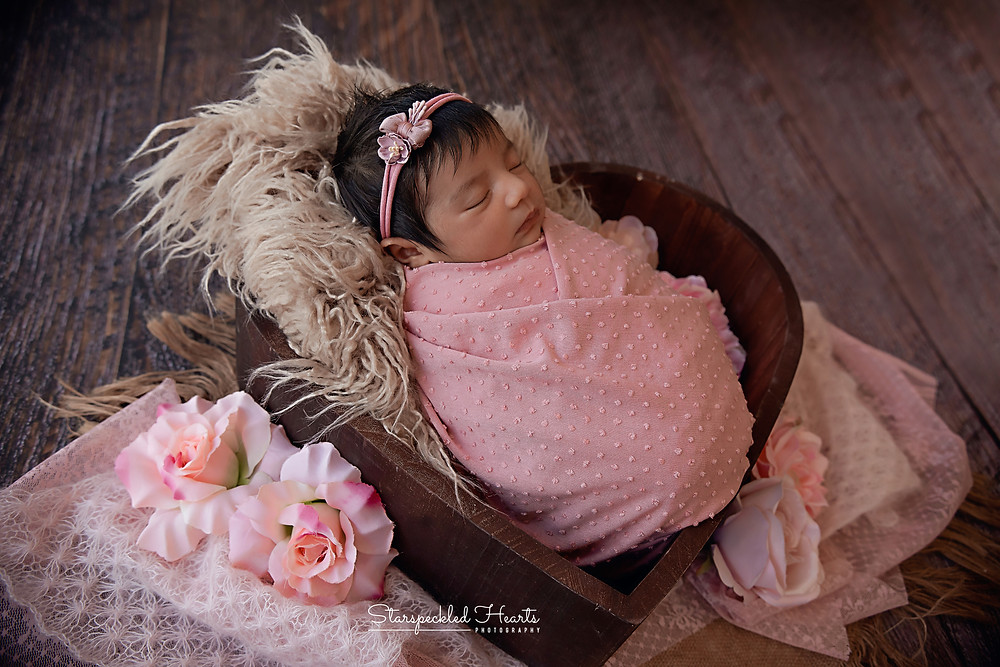 sleeping newborn baby swaddled in a pink wrap, lying in a heart shaped bowl surrounded by pink flowers for her newborn photography session with starspeckled hearts photography