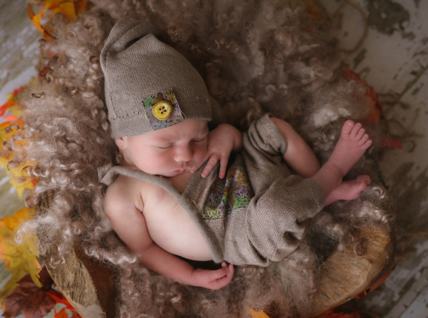 sleepy curled up newborn baby wearing romper and hat
