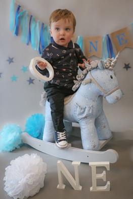 little boy sitting on blue rocking horse