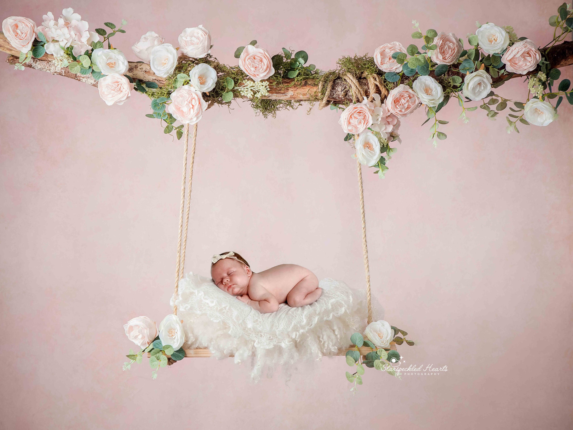 sleeping baby girl laying on her front on a floral swing