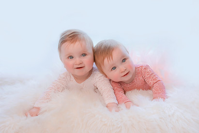 baby twin sisters lying on a white fluffy rug