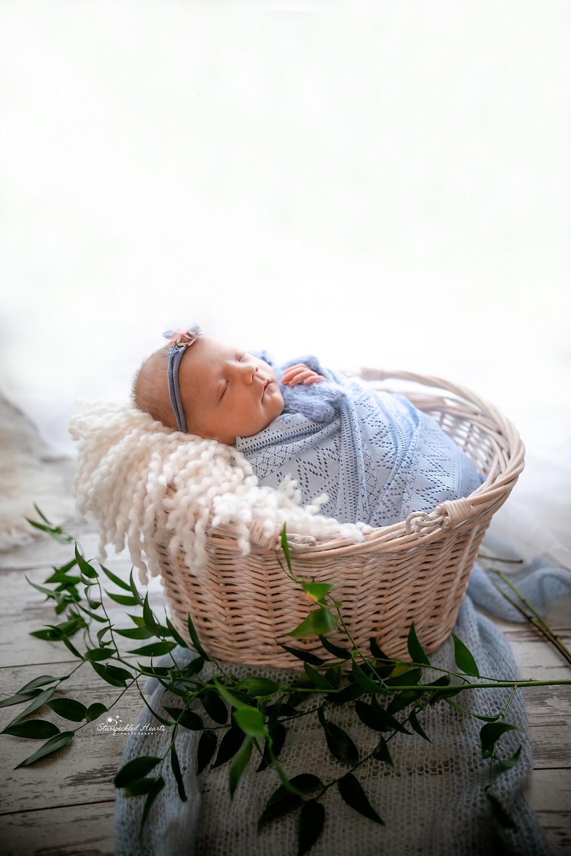 beautiful sleeping baby girl wearing a blue wrap