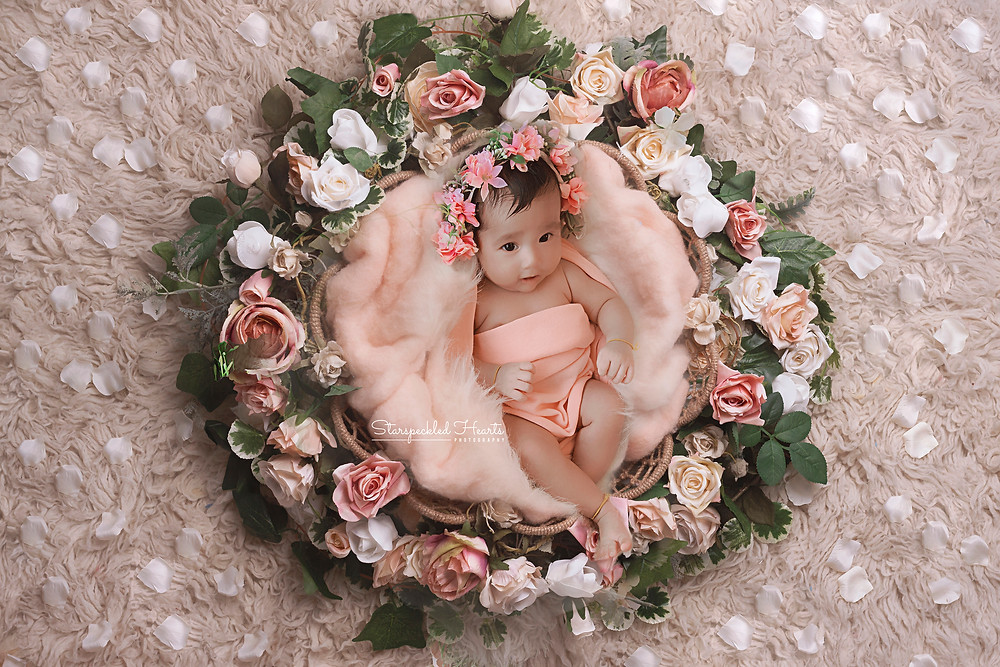 newborn baby girl with a pink floral headpiece lying in a large basket surrounded by flowers for her newborn photography session with starspeckled hearts photography in aldershot, hampshire