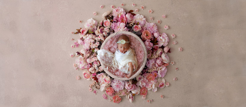 gorgeous baby girl wearing white lace wrap and floral headband, lying in a bowl surrounded by pink flowers by Starspeckled Hearts Photography