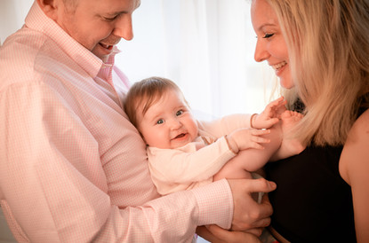 a family portrait with both mum and dad holding their baby girl, all smiling
