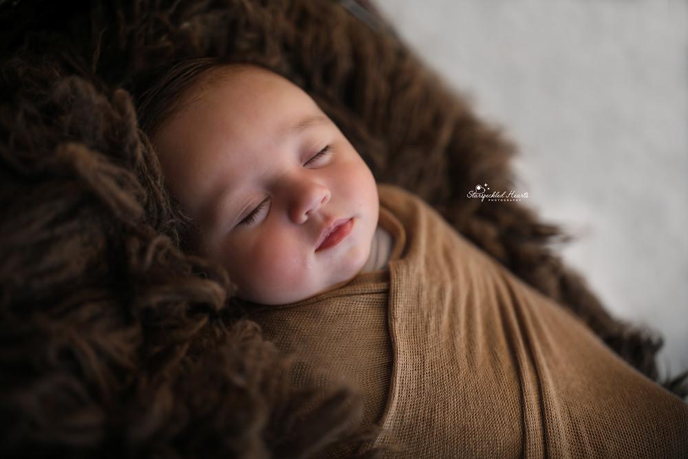 cute sleeping newborn wrapped in brown, lying on a dark brown rug