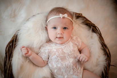 smiling baby girl dressed in a lacy romper lying in a wicker basket for her baby photography session with starspeckled hearts photography in aldershot, hampshire