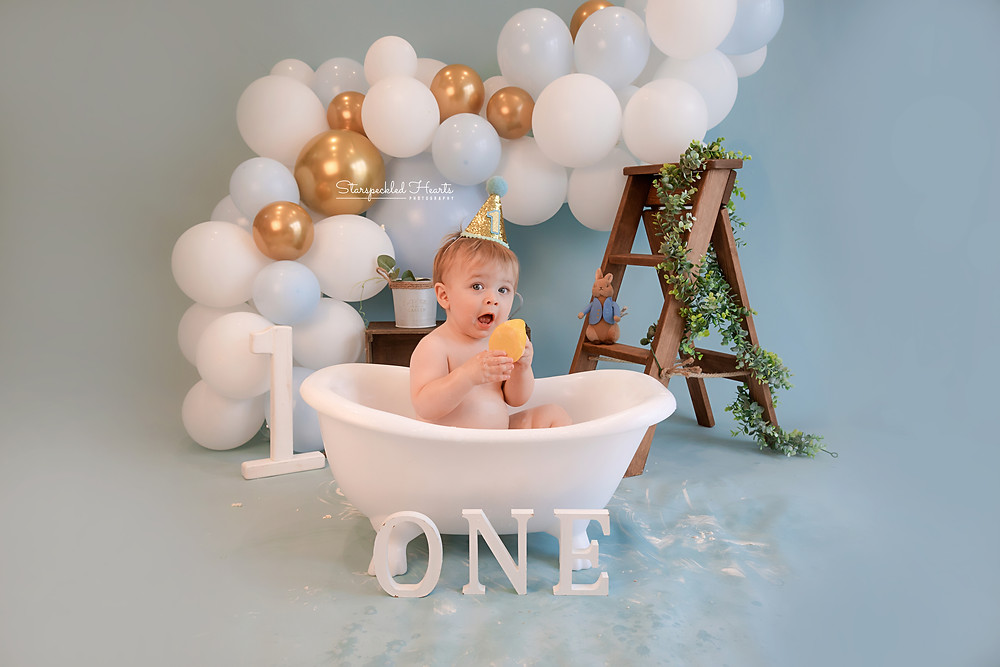 baby boy sitting in a claw footed tub with balloons behind him, for his cake smash session near me hampshire surrey