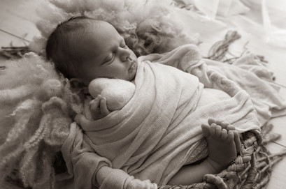 newborn sleeping in wicker basket holding a large felted heart, in black and white