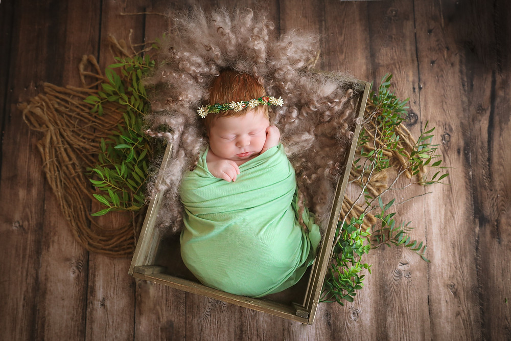 sleeping newborn girl in green wearing floral wreath