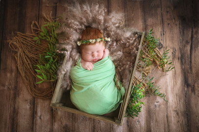 newborn lying in brown crate, wrapped in green wearing a floral wreath