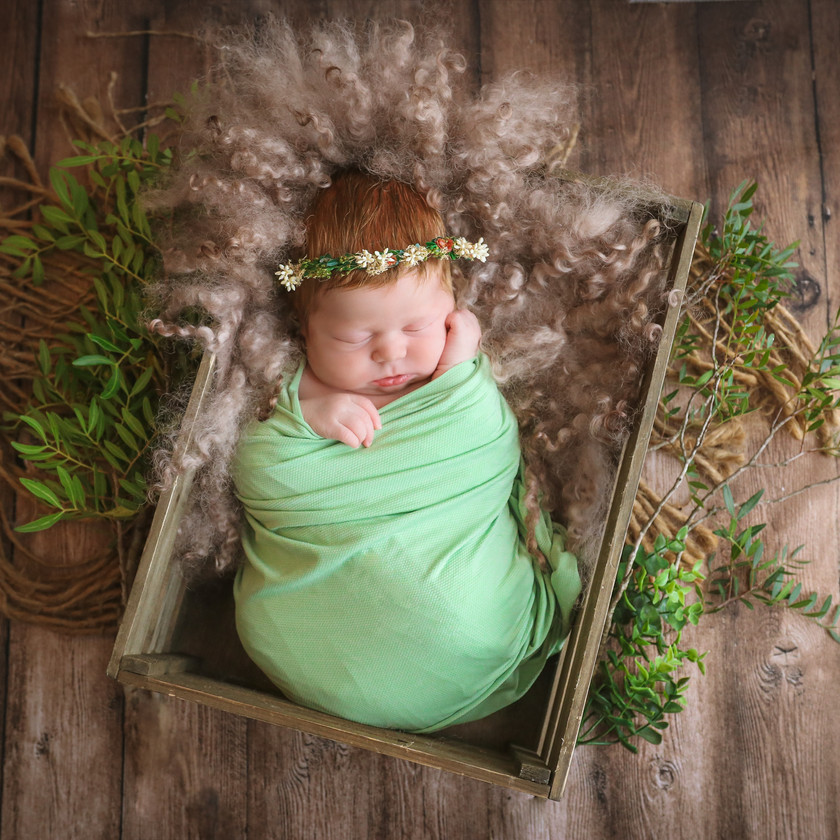 beautiful sleeping newborn girl with auburn hair, wrapped in green and wearing a matching floral crown, lying in a wooden crate surrounded by greenery