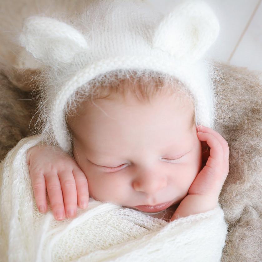 closeup of newborn wearing white bear bonnet