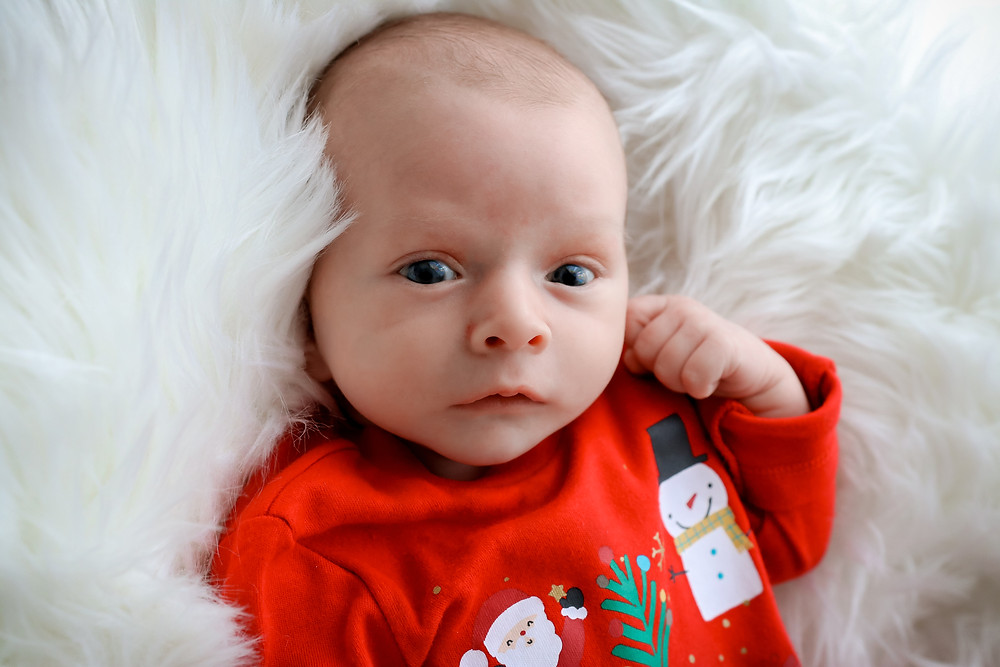 sweet newborn with wide open big blue eyes wearing a red christmas sleepsuit with a snowman and santa on, lying on a white fluffy rug