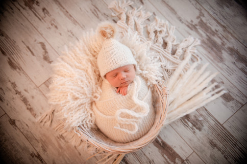 baby girl wrapped up in white lying in a basket surrounded by reeds