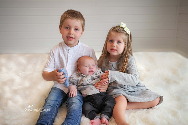 a boy and girl sitting on a white rug holding their baby brother between them