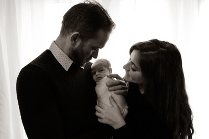 a man and woman wearing all black holding a swaddled newborn in their arms, both gazing lovingly down at their baby, in black and white
