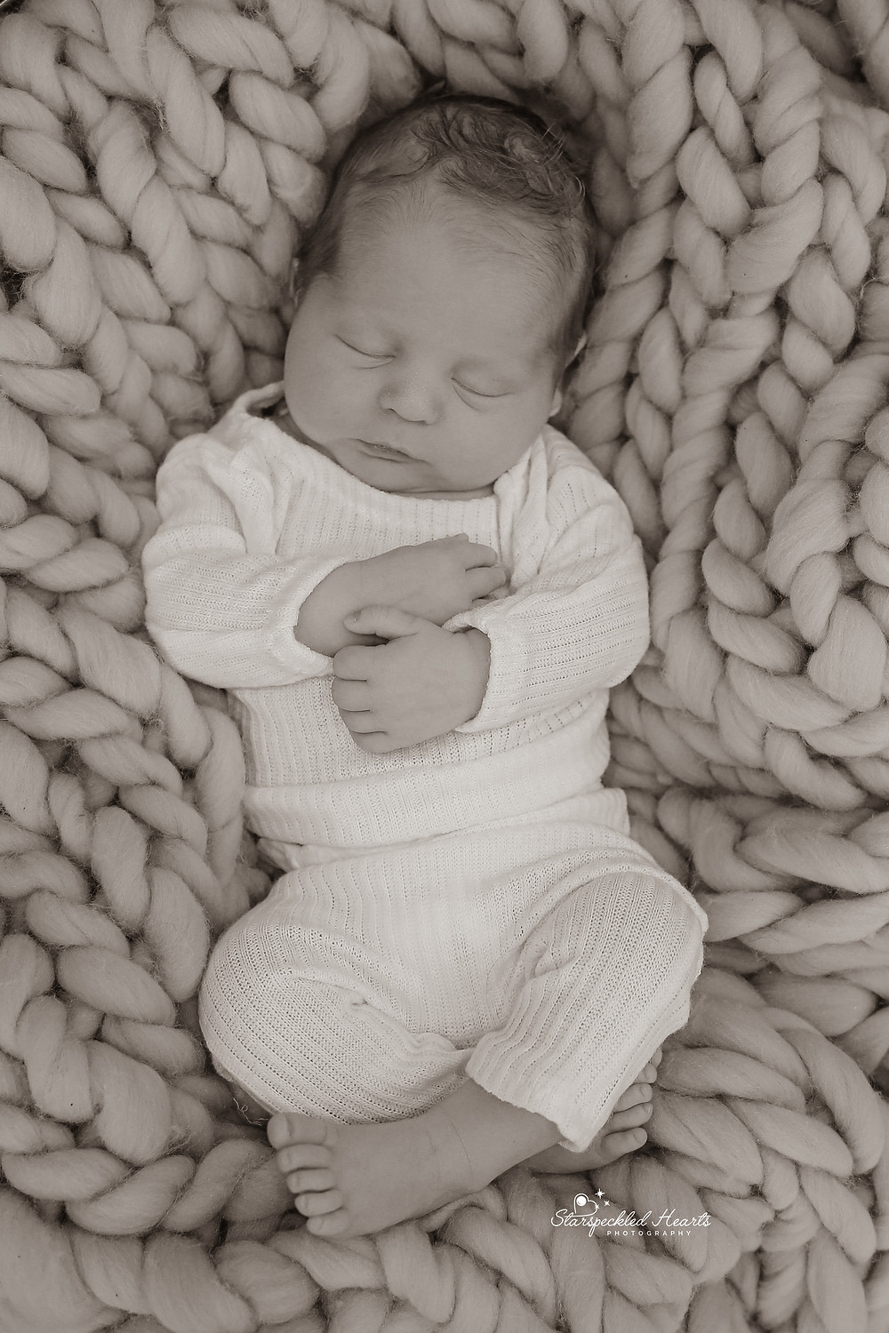 adorable sleeping baby boy, laying on a cable knit blanket