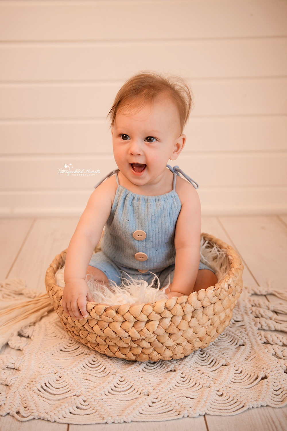 adorable baby boy wearing a blue ribbed romper, sitting in a basket